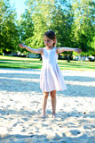 Girl in a sandbox. In the park in summer sunny day Royalty Free Stock Image