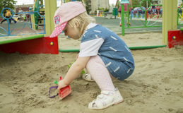The girl in the sandbox. Girl playing in the sandbox close-up Stock Photos