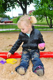 The girl in the sandbox. In the summer playing with toys Royalty Free Stock Images