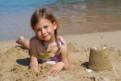 Girl with sandcastle. Pretty young girl lying next to a sandcastle she has made on the beach Royalty Free Stock Photography