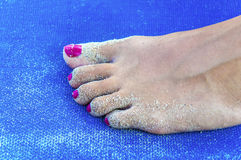 Girl sandy feet on sunbed close. Up Stock Images