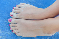 Girl sandy feet on sunbed close. Up Stock Photography