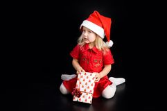 Girl in santa cap with gift Stock Photos
