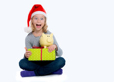 Girl with Santa- cap gift and piggy bank Royalty Free Stock Image