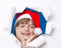 Girl with santa cap looking out of a hole in a paper Stock Photos