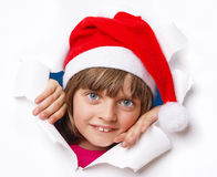 Girl with santa cap looking out of a hole in a paper Stock Images