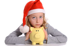 Girl with Santa- cap and piggy bank Royalty Free Stock Photos