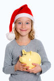 Girl with Santa- cap and piggy bank Royalty Free Stock Image