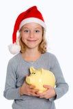 Girl with Santa- cap and piggy bank Royalty Free Stock Image