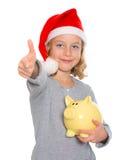 Girl with Santa- cap, piggy bank and thumb up Stock Photo