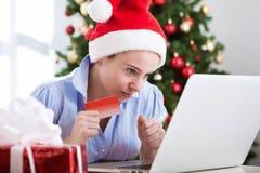 Girl with santa cap shopping online at home Stock Photos