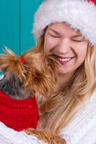 Girl in santa cap with yorkie dog in red sweater Stock Photography