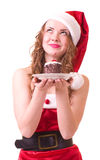 Girl in Santa Claus clothes with tasty cake Royalty Free Stock Photo