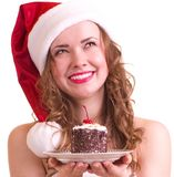 Girl in Santa Claus clothes with tasty cake Royalty Free Stock Image