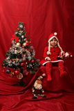 Girl with Santa Claus costume playing with a Christmas tree Royalty Free Stock Photos