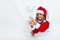 Girl in santa claus costume pointing to copy space. Through an opening in billboard Royalty Free Stock Images