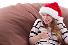 Girl in the Santa Claus hat and glass of champagne. Stock Image