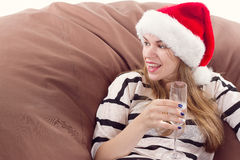Girl in the Santa Claus hat and glass of champagne. Royalty Free Stock Photography