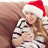 Girl in the Santa Claus hat and glass of champagne. Royalty Free Stock Photos