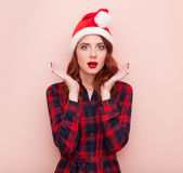 Girl in Santa Claus hat. Redhead girl in Santa Claus hat on pink background Royalty Free Stock Photos