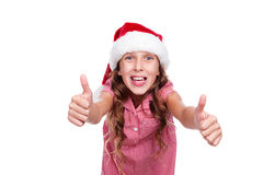 Girl in santa claus hat showing thumbs up Royalty Free Stock Photo