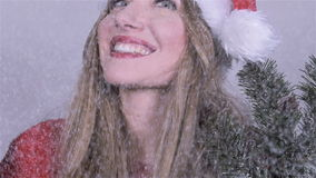 Girl in santa claus hat with tree branches enjoying snowfall. stock video footage