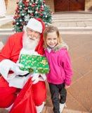 Girl And Santa Claus Holding Gift Royalty Free Stock Photos