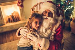 Girl with Santa Claus. Little charming girl with happy Santa Claus in beautiful house decorated for Christmas. Child is sitting on Santa`s lap and hugging him stock image