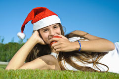 Girl in Santa claus red hat lying on a grass Royalty Free Stock Image