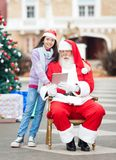 Girl With Santa Claus Using Digital Tablet Royalty Free Stock Photography