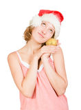 Girl in a santa clause cap with golden apple Royalty Free Stock Image