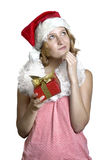 Girl in a santa clause cap with present Royalty Free Stock Photo