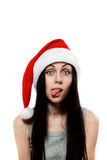 Girl in Santa Clause hat put out one's tongue Stock Photography