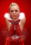 Girl in santa cloth blowing snow. Attracive girl in santa cloth blowing snow from hands Royalty Free Stock Images