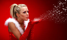 Girl in santa cloth blowing snow Stock Images