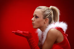 Girl in santa cloth blowing snow Stock Image