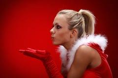 Girl in santa cloth blowing snow. Attracive girl in santa cloth blowing snow from hands Stock Image