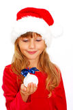 Girl in santa cloth with christmas ball in hand Royalty Free Stock Photos