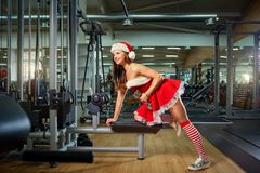 Girl in Santa costume with dumbbells in the gym on Christmas. royalty free stock image