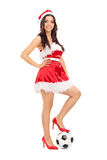 Girl in Santa costume with football under her foot Stock Image