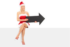 Girl in Santa costume holding an arrow seated on a panel Royalty Free Stock Photos