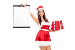 Girl in Santa costume holding gifts and clipboard Royalty Free Stock Photography