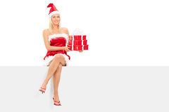 Girl in santa costume holding gifts seated on panel Royalty Free Stock Images