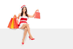 Girl in Santa costume holding shopping bags. Seated on a panel isolated on white background Stock Image