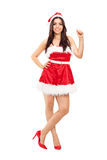 Girl in Santa costume leaning against a wall Stock Photo