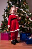 Girl in Santa costume near Christmas tree Stock Image