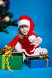 Girl in Santa costume playing with gifts Royalty Free Stock Images