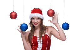 Girl in santa dress and christmas balls Stock Image