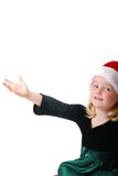 Girl in Santa hat. Young Caucasian girl in a Santa hat holding out her hand Royalty Free Stock Image