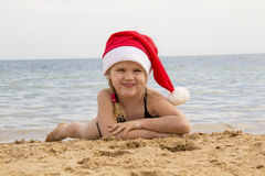 Girl in santa hat on the beach Royalty Free Stock Images
